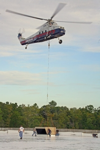 : Aircrane, Inc. S-58T helicopter positioning an air conditioning unit on                                top of a building in Palm Coast, Florida. (Picture from www.aircrane.com )