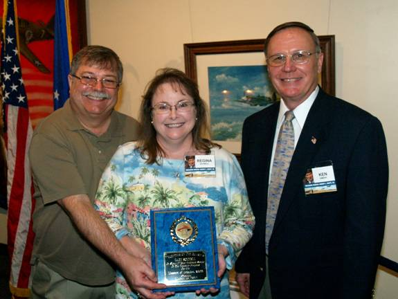 Museum Director Ken Emery, right, congratulates Gary Schnell, left, and his wife Regina at the Museum of Aviation foundation board meeting on March 15.Schnell was named Volunteer of the Quarter for the first quarter of 2012.