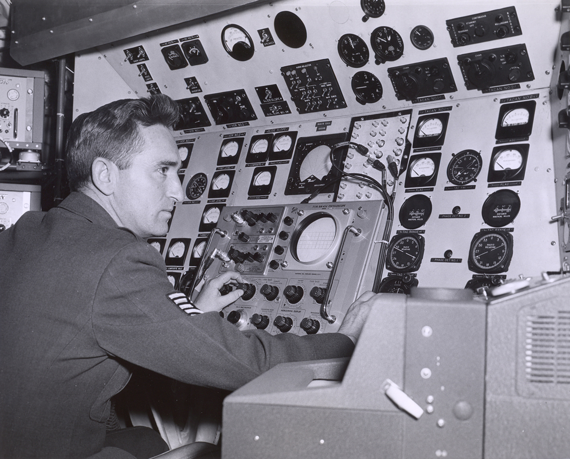 A technician checks the test console inside an Air Force Communications Service C-140A.