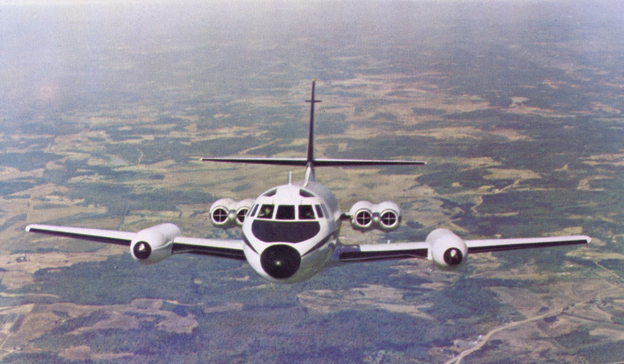 "Front view of a JetStar in flight. Distinctive features include the four engines mounted  on the rear fuselage, two per side, and the ""slipper tanks"" on the wings that carried fuel."