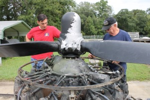 Museum restoration supervisor Tony Day (left) and restoration volunteer Bob Denison look at one of the B-17's engines.